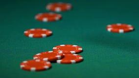 Röda chiper som faller på skrivbordet, person som tillfredsställs med den modiga segern för kasino, närbild lager videofilmer