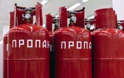 Röda cylindrar av propangas Inskriften i ryskt - propan arkivfoton
