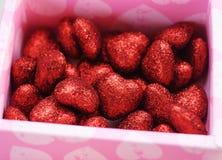 Röda dekorativa hjärtor i en rosa ask som göras av papp, Arkivbild