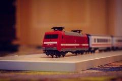 Röda drevbarns leksak, bilar på golvet royaltyfria foton