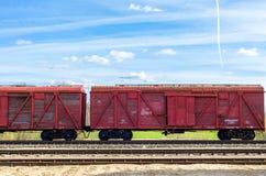 Röda drevvagnar på järnväg Arkivbild