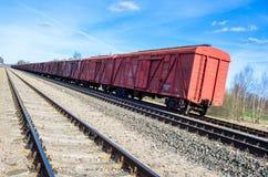 Röda drevvagnar på järnväg Arkivfoto