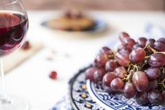 Röda druvor för grupp i blå bunke, exponeringsglas av rött vin, mot suddighetsbakgrund royaltyfria foton