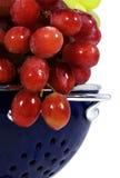 Röda druvor i blå durkslag arkivfoton