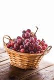 Röda druvor i stucken korg Arkivfoto