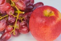 Röda druvor och rött äpple mot vit bakgrund arkivfoto