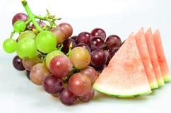 Röda druvor och vattenmelon som isoleras på vit bakgrund Arkivbild