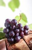 Röda druvor på den lantliga trätabellen Royaltyfri Foto