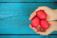 Röda easter ägg i händerna Fotografering för Bildbyråer