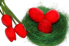 Röda easter ägg och röda tulpan Fotografering för Bildbyråer