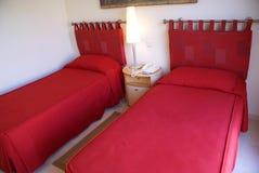 Röda enkla sängar royaltyfria bilder