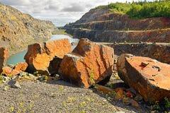 Röda enorma stenar i en övergiven min Arkivfoto