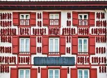 Röda Espelette pepprar uttorkning i väggen av det baskiska huset Arkivbilder