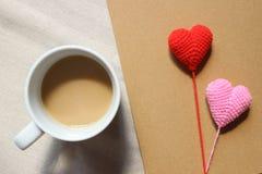 Röda förälskelsehjärtor på anmärkning för brunt papper med en kopp kaffe Royaltyfri Bild