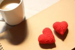 Röda förälskelsehjärtor på anmärkning för brunt papper med en kopp kaffe Arkivbilder