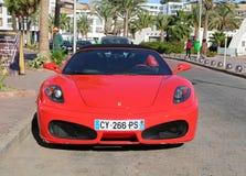 Röda Ferrari F 430 parkerade framme av havannacigarrrestaurang på Marina Agadir Arkivfoton
