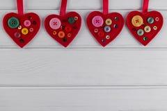 Röda filthjärtahantverk som dekoreras med pärlor och knappar på vit bakgrund Arkivbilder
