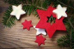 Röda filtstjärnor, kakor för vit jul och granfilialer på gammalt Arkivfoton