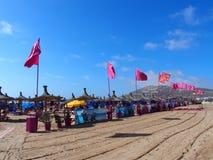 Röda flaggor på stranden i den loppAgadir staden i Marocko Arkivbild