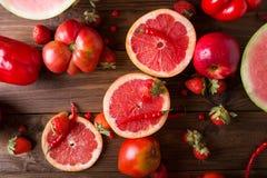 Röda frukter och grönsaker på en träbakgrund Arkivfoto