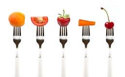 Röda frukter och grönsaker på samlingen av gafflar arkivbild