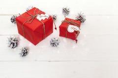 Röda gåvaaskar med sörjer kottar på en vit trätabell Christma arkivfoto