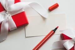 Röda gåvaaskar som binds med ett vitt band, en markör och kortet med kopieringsutrymme på en ljus bakgrund arkivfoto
