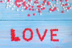 Röda godishjärtor som lägger på ljus - blått målade lantlig träbakgrund Fotografering för Bildbyråer