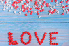 Röda godishjärtor som lägger på ljus - blått målade lantlig träbakgrund Royaltyfria Foton