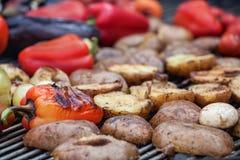 Röda gröna spanska peppar, potatisar, champinjoner, tomater och aubergine som grillas till guld- brunt Arkivbild