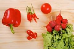 Röda grönsaker på en träbakgrund Arkivbild