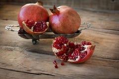 Röda granatäpplen på en platta på den gamla trätabellen Fotografering för Bildbyråer