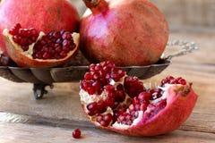 Röda granatäpplen på en platta på den gamla trätabellen Arkivbilder