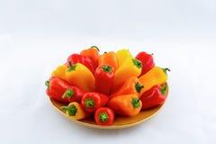 Röda, gula och apelsinpeppar på en platta Arkivbild