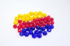 Röda, gula och blåa pärlor på en vit bakgrund För hantverk och hobbyer royaltyfria foton