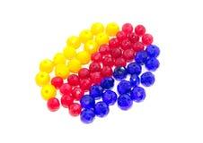 Röda, gula och blåa pärlor på en vit bakgrund För hantverk och hobbyer arkivbilder
