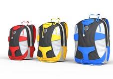 Röda, gula och blåa ryggsäckar på vit bakgrund Arkivbilder