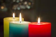 Röda, gula och gröna färgglade stearinljus med suddig bokehbackg Arkivfoto