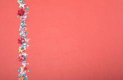 Röda, gula och gröna hjärta- och cirkelkonfettier på en RÖD bakgrund Högt upplösningsfoto Royaltyfri Fotografi