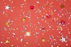 Röda, gula och gröna hjärta- och cirkelkonfettier på en RÖD bakgrund Högt upplösningsfoto Arkivfoto