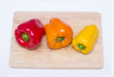 Röda, gula, orange hela spanska peppar på en skärbräda Royaltyfria Bilder