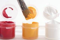Röda gula vita akrylmålarfärger och målarpensel Royaltyfri Bild