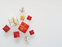 Röda, guld- och silvergåvaaskar på vit bakgrund Arkivfoto