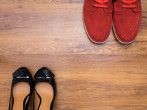 Röda gymnastikskor och svarta kvinnors skor fotografering för bildbyråer