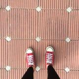 Röda gymnastikskoskor som går på smutsig konkret bästa sikt, kanfasskor som går på betong Arkivfoton