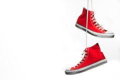 Röda hängande gymnastikskor Fotografering för Bildbyråer