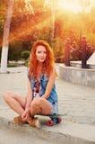 Röda haired unga kvinnor som sitter på skateboarden med henne ben, korsade bakbelyst vid solen Royaltyfri Bild