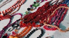 Röda halsband med andra smycken som är till salu i tappningen, shoppar arkivbild