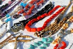 Röda halsband med andra smycken som är till salu i tappningen, shoppar royaltyfri foto