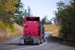 Röda halva lastbilar tillbaka eskorterar på spolningsnedgångvägen Arkivbild